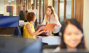Two women talking in an office environment